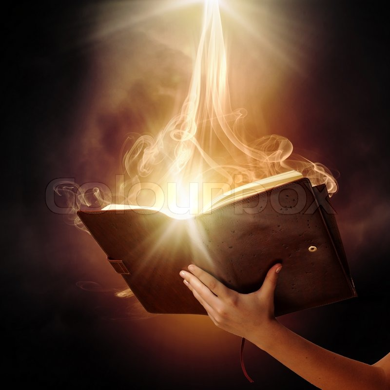 Stock image of 'Human hand holding magic book with magic lights'
