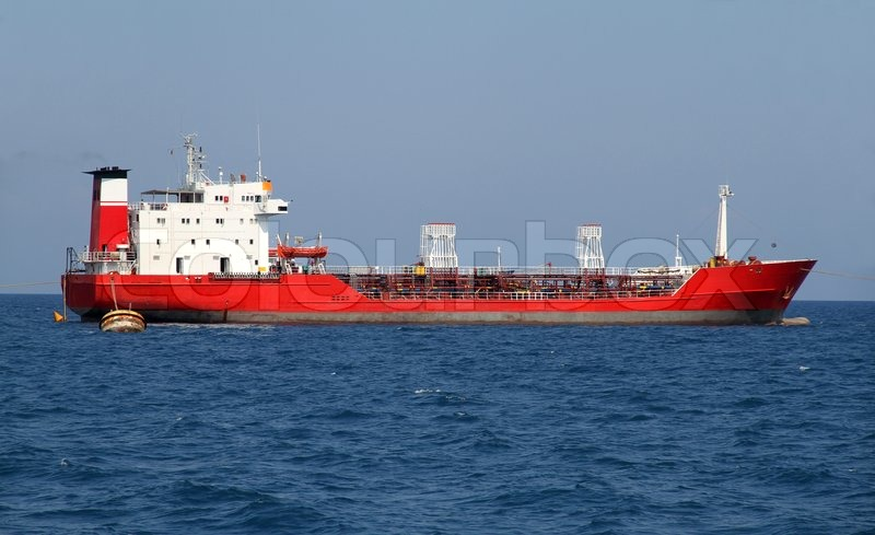 Red tanker designed for transporting crude oil is at anchor near the port, stock photo