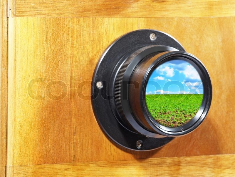 Old camera lens with blue sky and green grass inside, stock photo