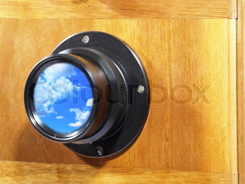 Old camera lens with blue sky and clouds inside, stock photo