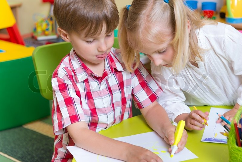Two cute little prescool kids drawing with crayons at the table, stock photo