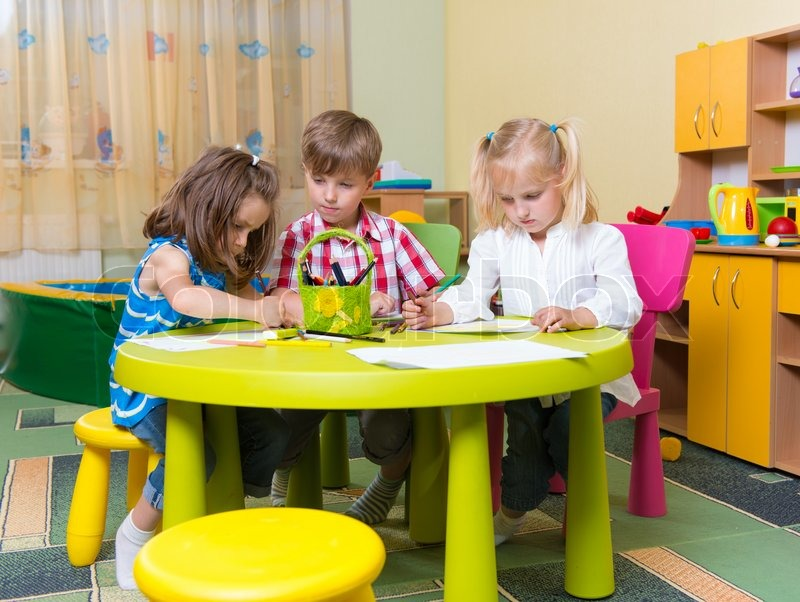 Kinder Garden: Group Of Cute Little Prescool Kids Drawing With Crayons At