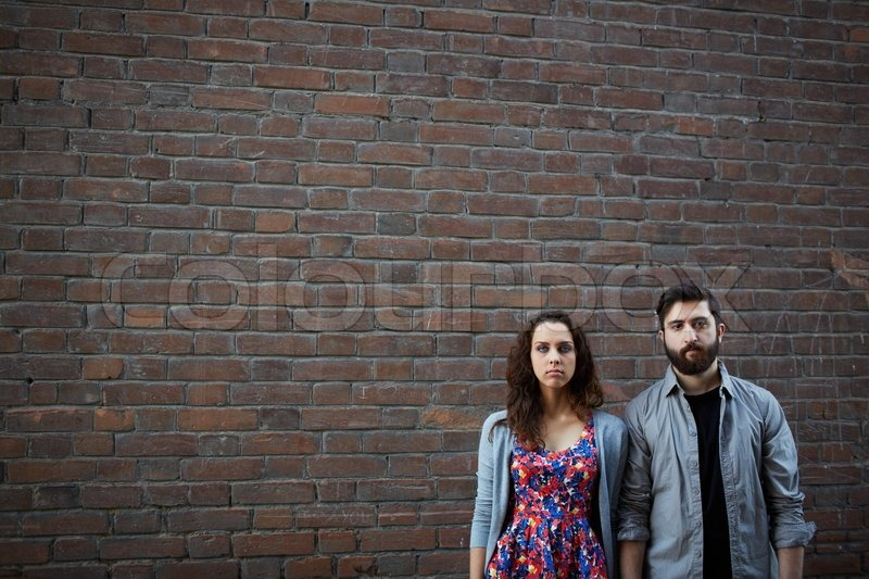 Portrait of serious couple standing by the brick wall, stock photo
