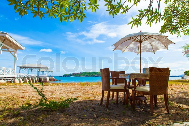 Chairs and table under umbrella Near the sea At the bright air. On of Weekend, stock photo