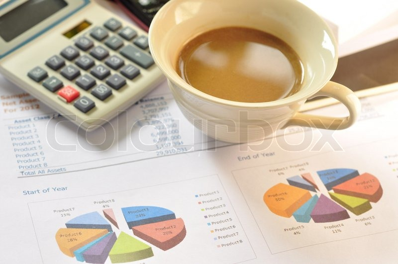 Coffee on financial statements and line chart, stock photo