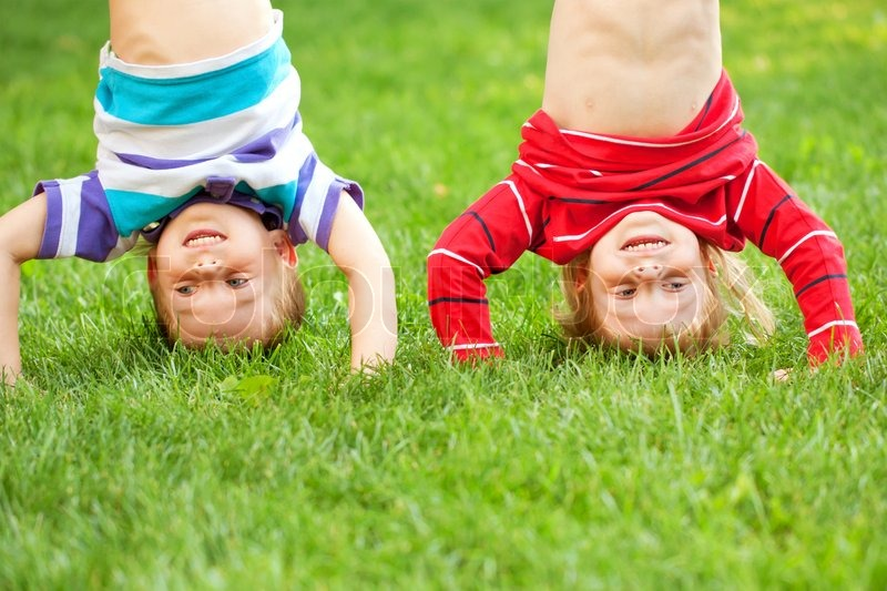 Happy children standing upside down on the grass. Fun kid\'s holiday, stock photo