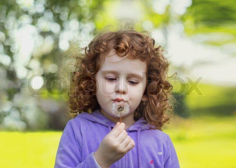 Beautiful little curly girl blowing dandelion, horizontal shot, stock photo