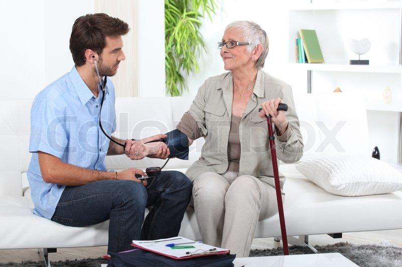 Ung mand tager blodtryk på en ældre  | Stock foto