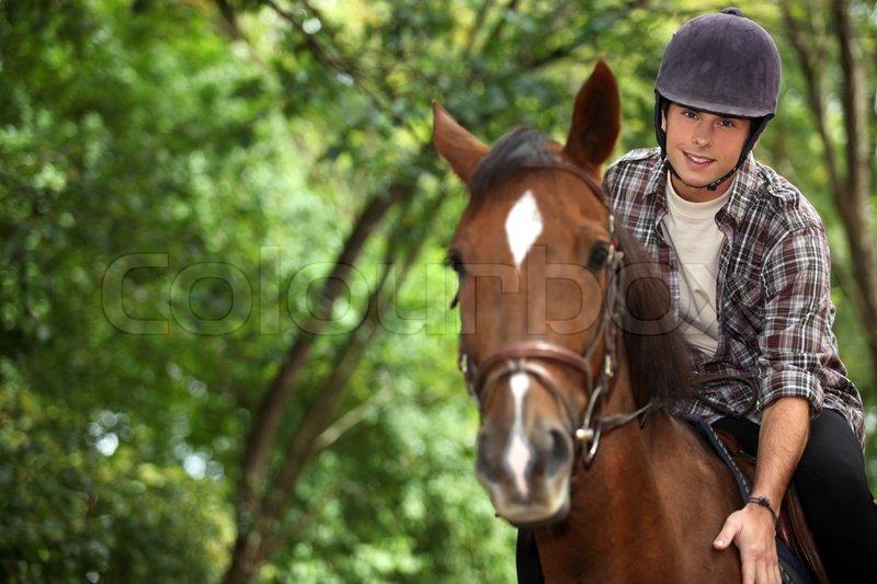 Young man riding horse, stock photo