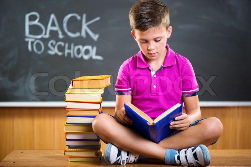 Cute school boy reading book in classroom against ...