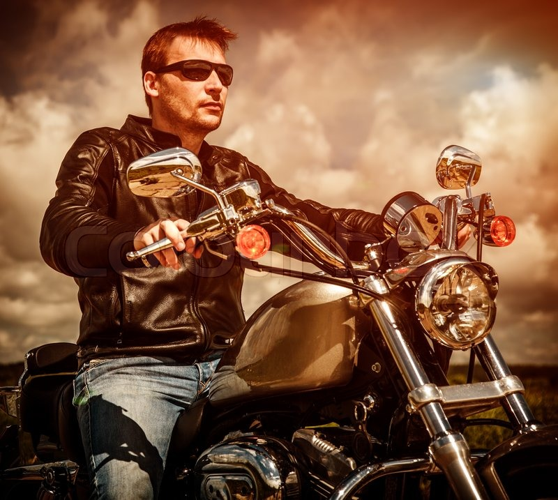Biker man wearing a leather jacket and sunglasses sitting on his motorcycle looking at the sunset, stock photo