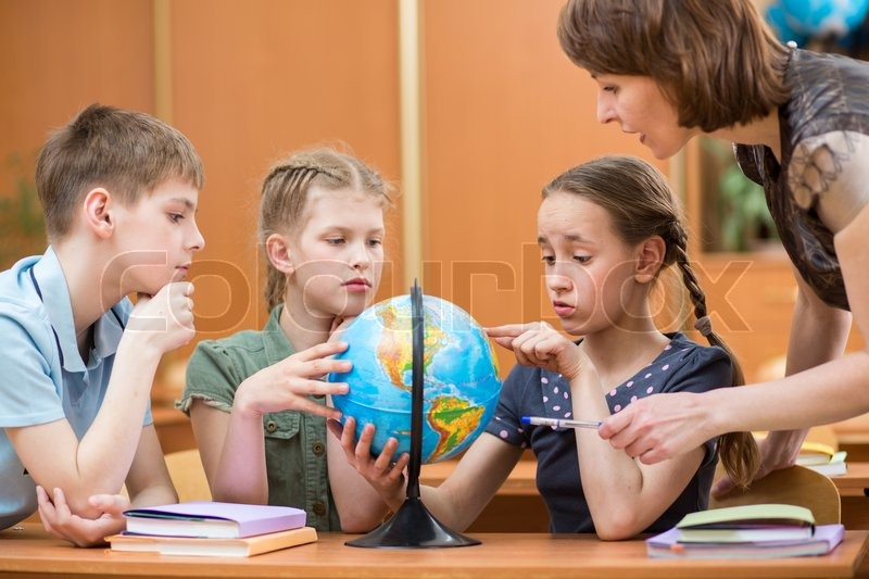 school kids studying a globe together with teacher stock photo