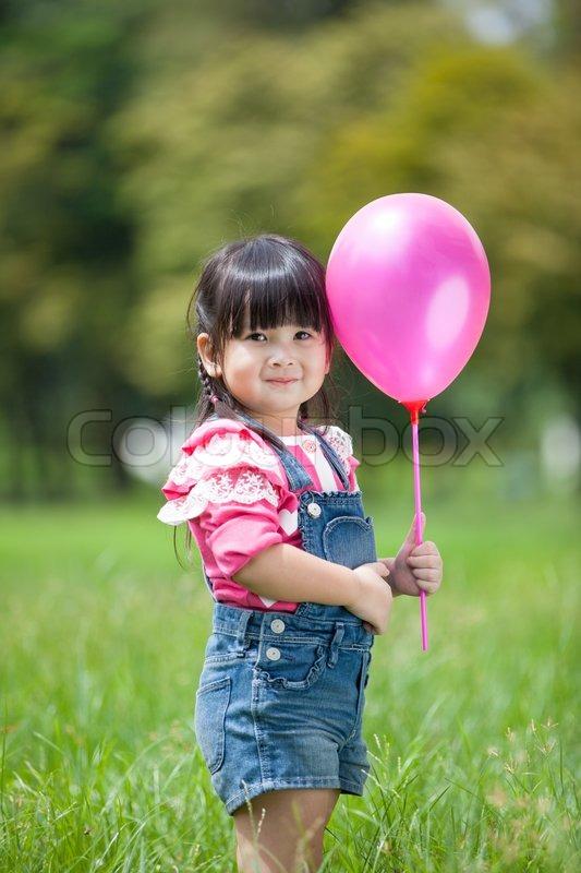 Asiatische mädchen spielen ballon im garten stockfoto
