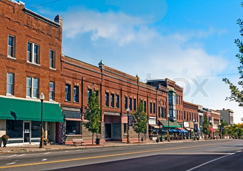 A photo of a typical small town main street in the United States of America. Features old brick buildings with specialty shops and restaurants. Decorated with autumn decor. , stock photo