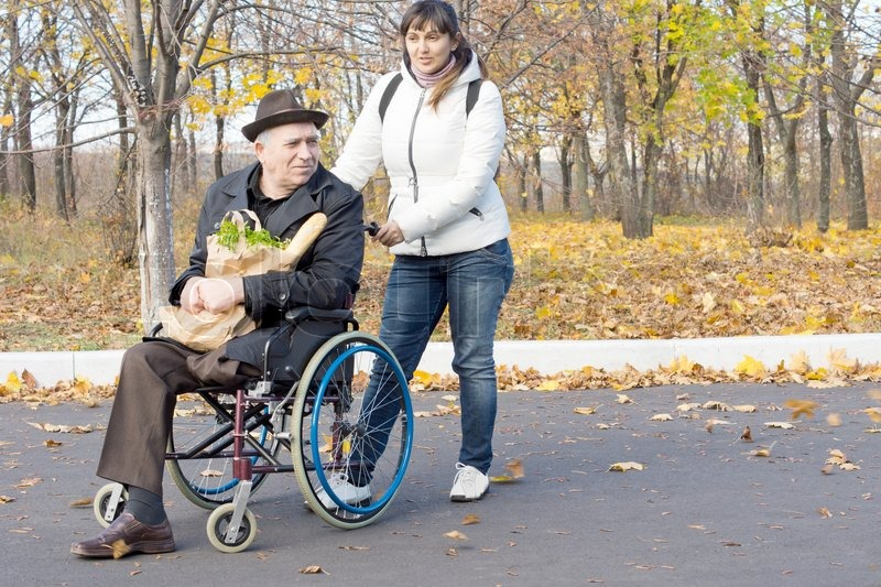 Woman helping a disabled pensioner in a wheelchair pushing House plans for disabled people
