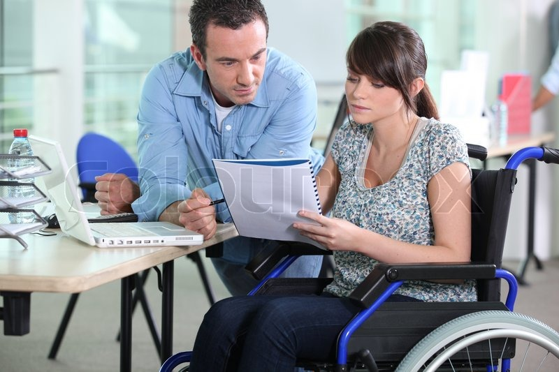 Stock image of 'Young woman in wheelchair working with a male colleague'