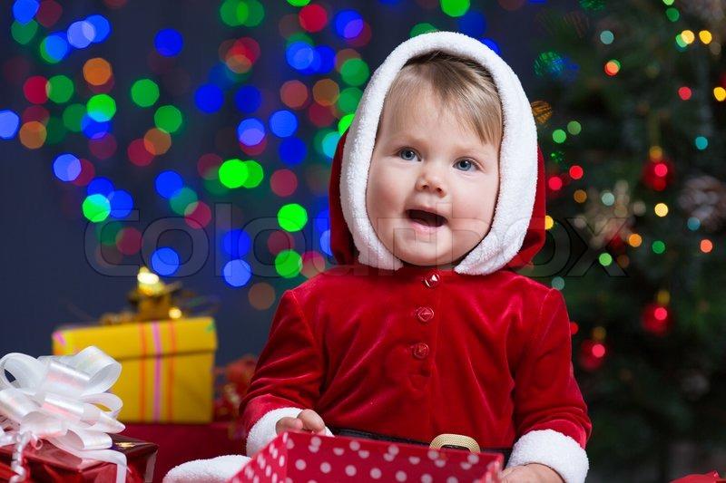 baby als weihnachtsmann verkleidet am weihnachtsbaum mit. Black Bedroom Furniture Sets. Home Design Ideas