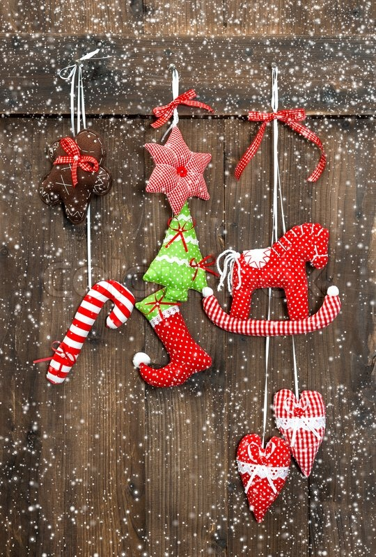 Christmas decoration handmade toys hanging over rustic wooden background. nostalgic retro style picture with falling snow effect, stock photo