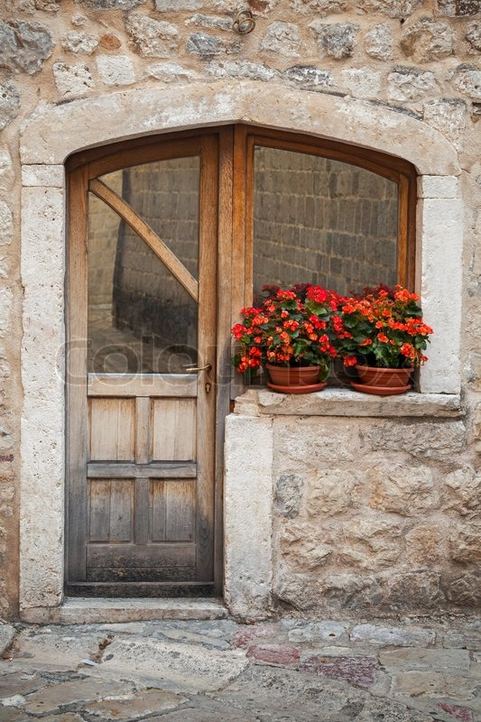Old Wooden Door With Red Flowers On The Windowsill Stock