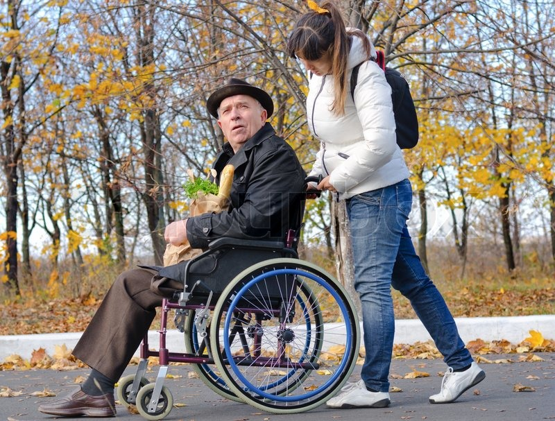 Smiling carer pushing an old man in a wheelchair stock photo image - Woman Pushing An Elderly Handicapped Man In A Wheelchair