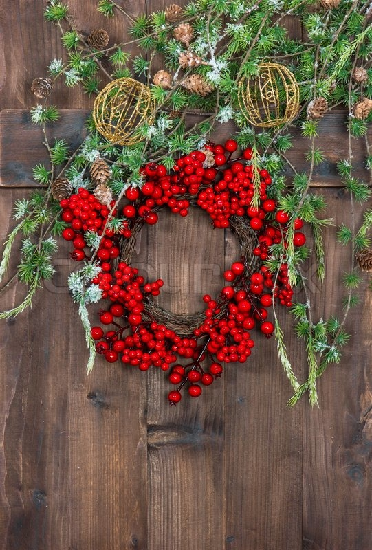 Green christmas tree branches and wreath from red berries, stock photo