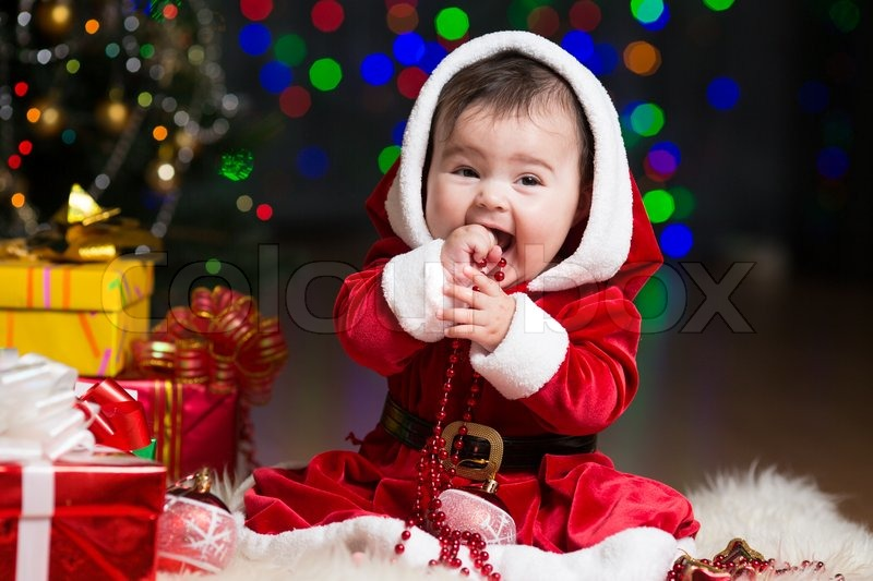 Kid girl dressed as Santa Claus at Christmas tree with gifts ...