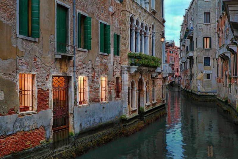 Small Canal Among Old Brick Traditional Venetian Houses With Illuminated Windows At Evening In