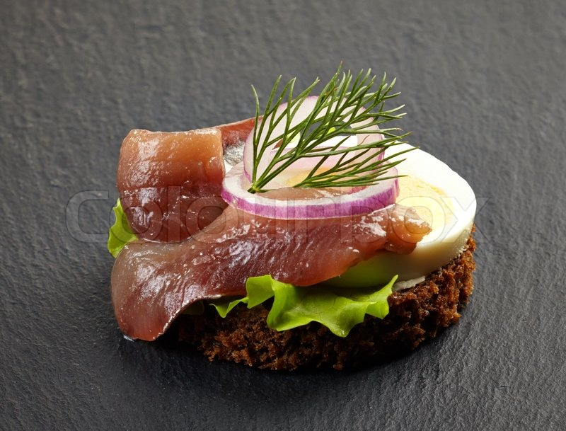 Canape with anchovy and egg on dark background stock for Canape suppliers