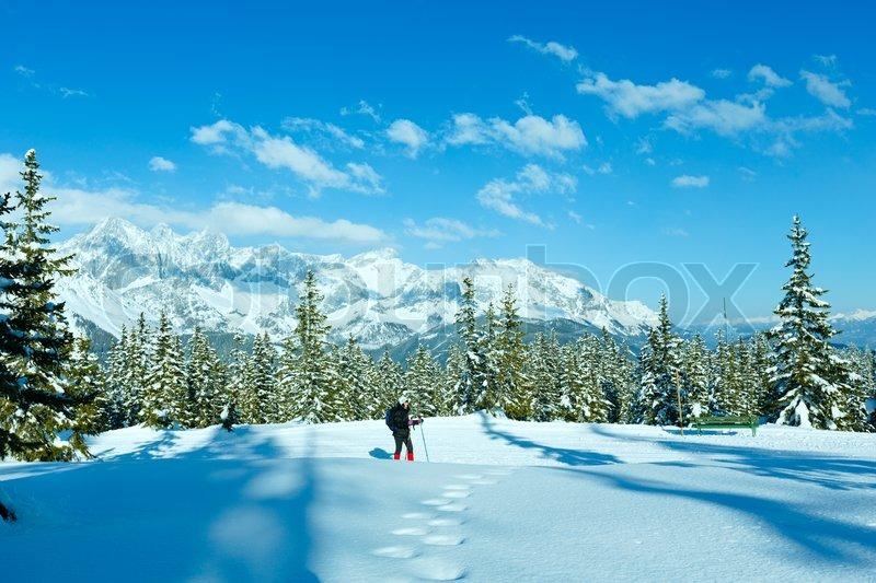 Winter mountain landscape and woman on walk top of Papageno bahn - Filzmoos, Austria, stock photo
