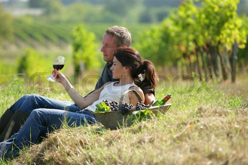 Couple tasting wine at a vineyard, stock photo