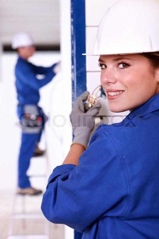 Female Electrician Installing A Power Stock Photo