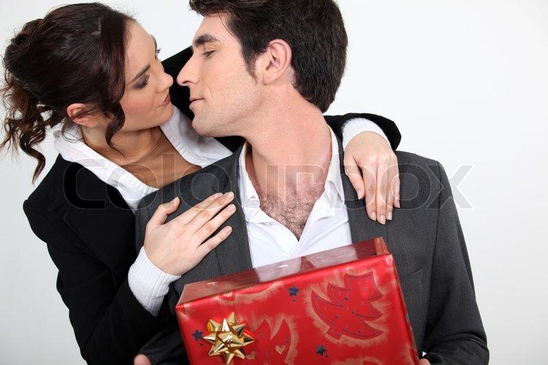 paar mit weihnachtsgeschenk zu k ssen stockfoto colourbox. Black Bedroom Furniture Sets. Home Design Ideas
