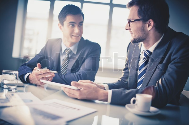 Image of two young businessmen communicating at meeting, stock photo