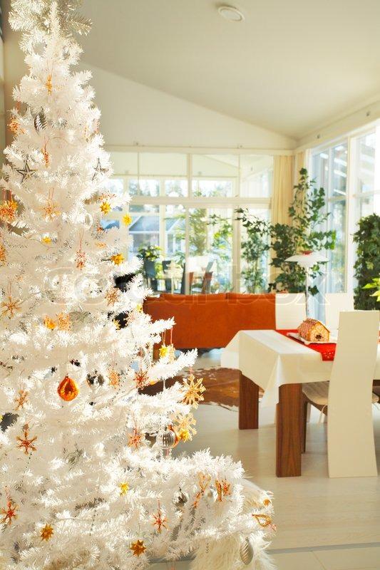 Skandinavisk stue med hvid kunstig pyntet juletræ i forgrunden ...