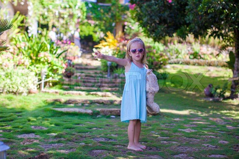 Little girl walking in tropical green hotel, stock photo