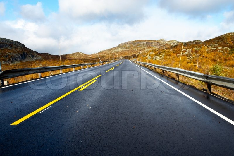 Empty mountain road road receding into the distance at the cloudy autumn day , stock photo