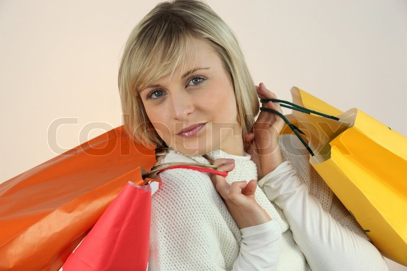 Stock image of 'Young woman with arms full of storebags'