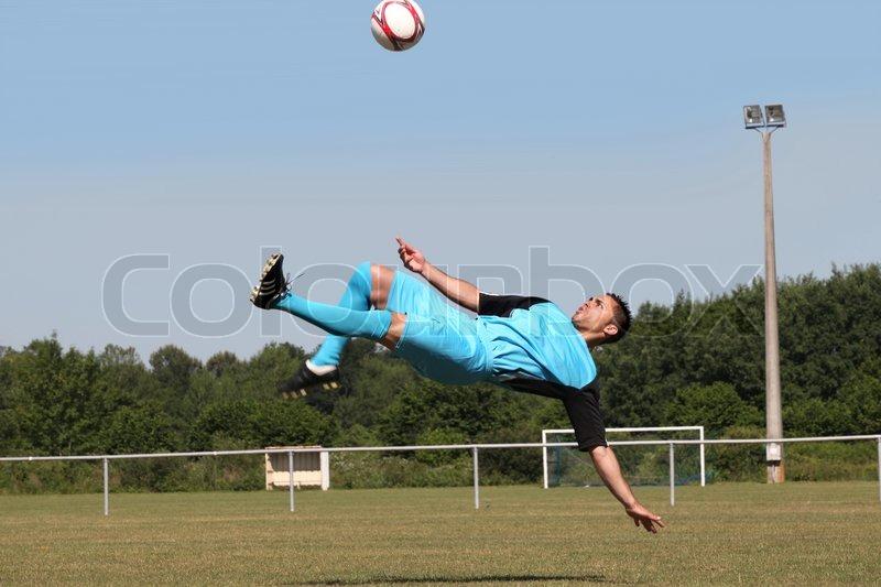Footballer in mid-air back kick, stock photo
