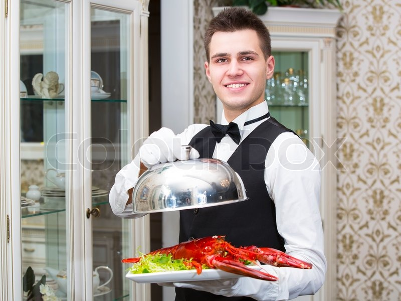 waiter with lobster on a plate in a restaurant stock photo colourbox