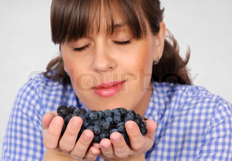 Stock image of 'Smelling grapes'