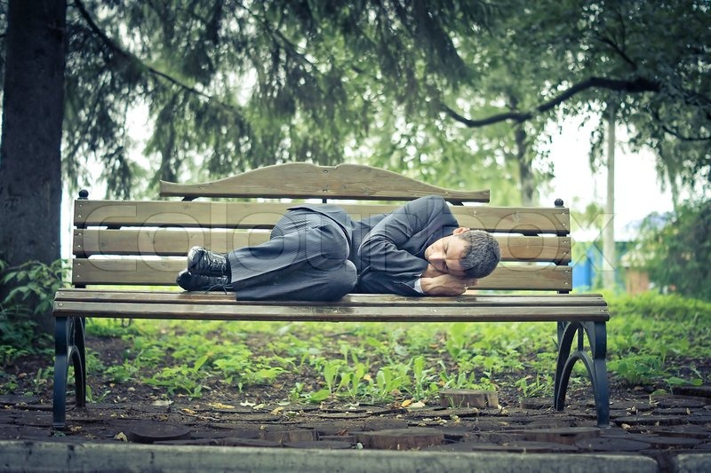 Man In A Suit Sleeping On The Street Stock Photo