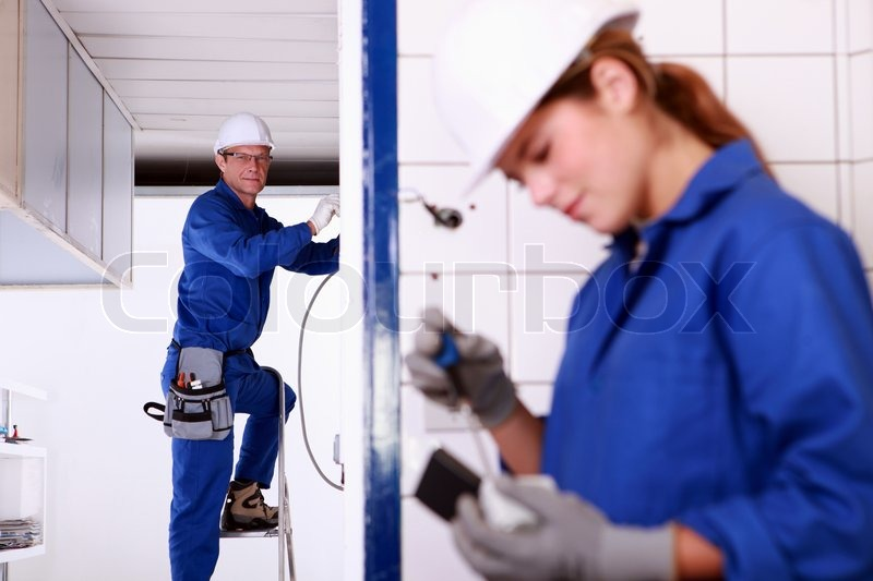 female electrician mentor supervising female electrical engineer stock photo