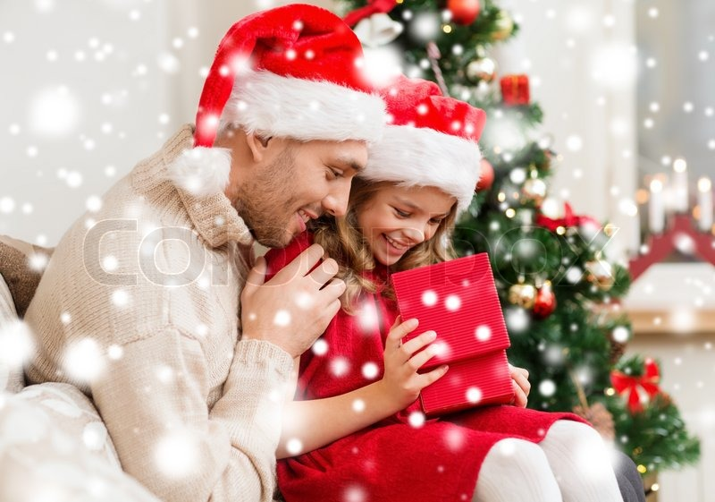 family christmas x mas winter happiness and people concept smiling father and daughter in santa helper hats opening gift box stock photo