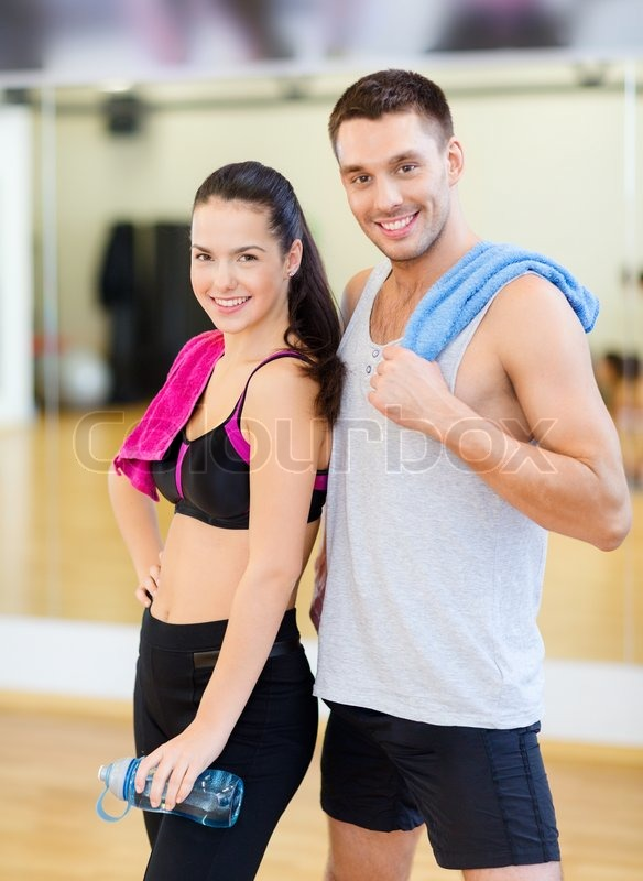 Fitness, sport, training, gym and lifestyle concept - two smiling people in the gym, stock photo