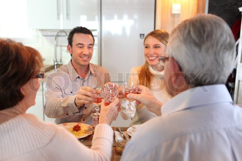 Four adults making a toast at dinner, stock photo