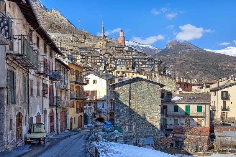 Stock image of 'Narrow street among old stone houses and mountains on background in Tende - small alpine town on French - Italian border.'
