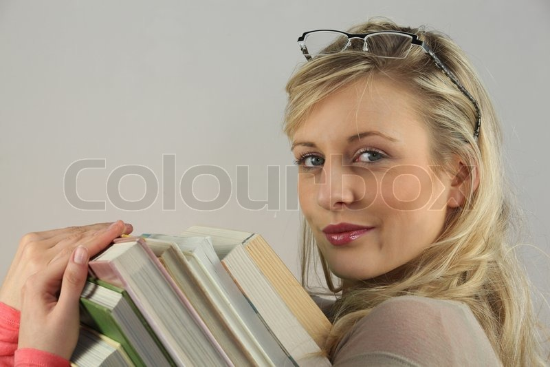Stock image of 'Young woman carrying a pile of books'