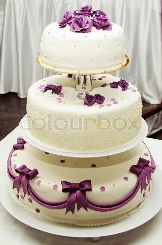 Weiße Hochzeitstorte mit lila Blume Detail  Stockfoto  Colourbox