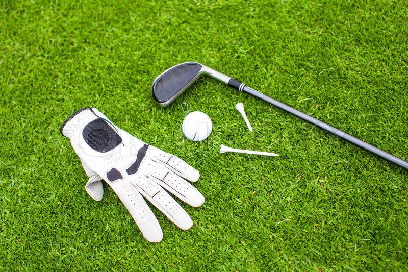 Golf equipment on green grass, stock photo