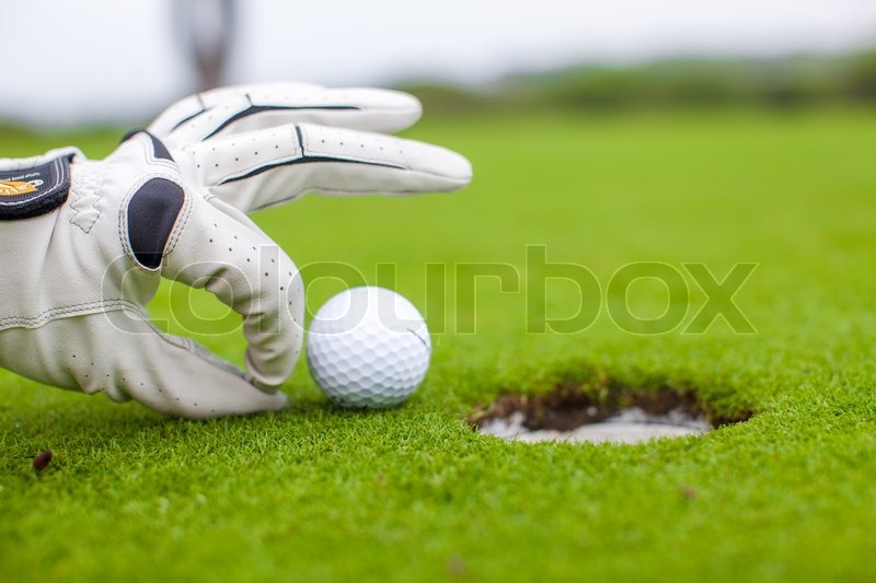 Golf player man pushing golf ball into the hole, stock photo